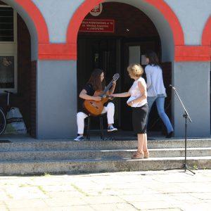 Julia daje popis na gitarze.